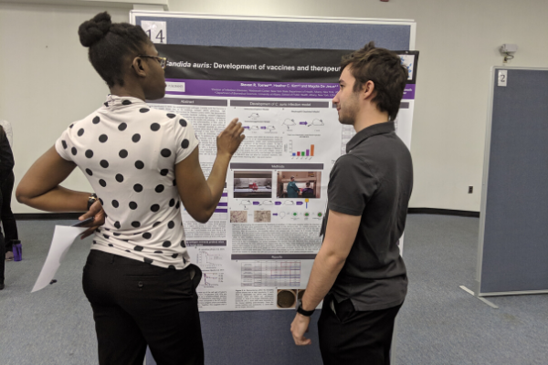 Two students talk in front of a research poster. One student wears a white shirt with black polka dots, and has her hand up as she explains the poster. The other student, wearing a grey shirt and black pants, stands and listens to the explanation of the poster.