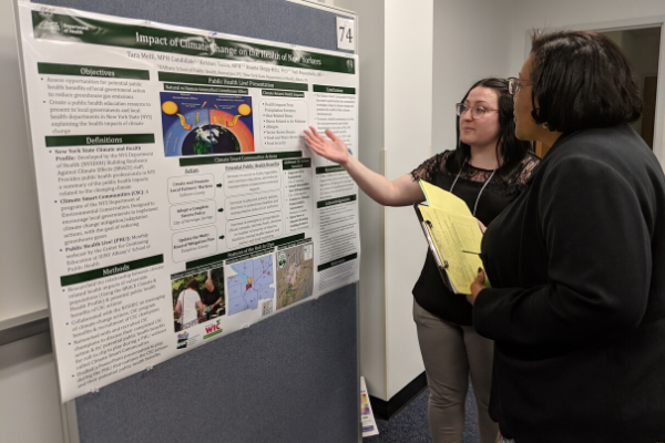 A student stands in front of her research/internship poster, explaining her work to a faculty member who listens attentively.