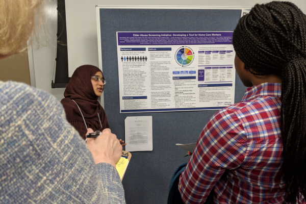 A student stands beside her poster, speaking with two women who are looking at her poster.