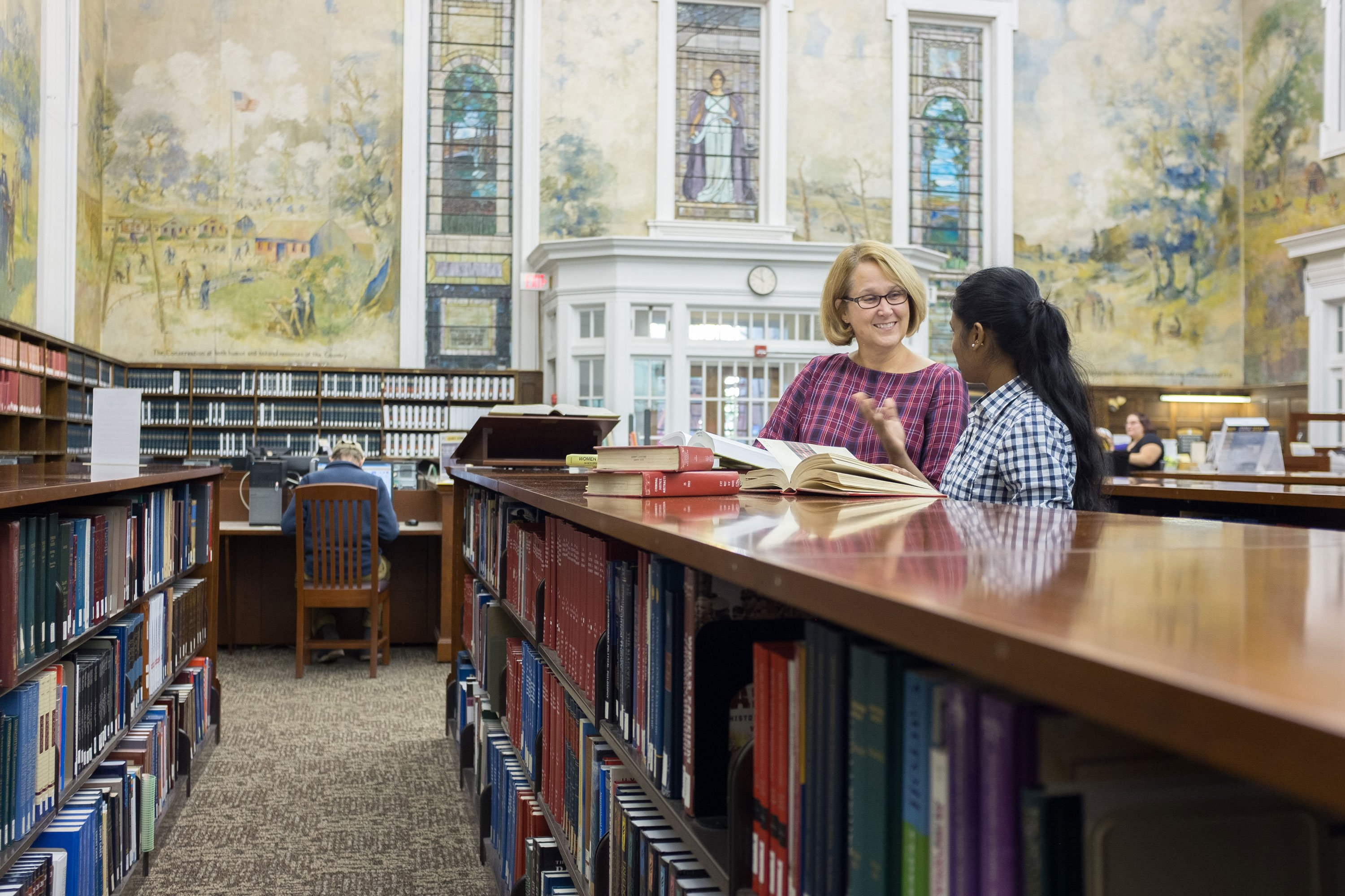 A student consults a staff member inside the Dewey Graduate Library on the Downtown Campus.