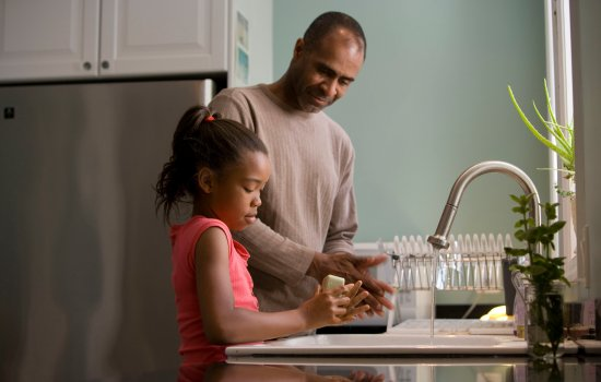 A man and his daughter stand at a sink, washing their hands together.