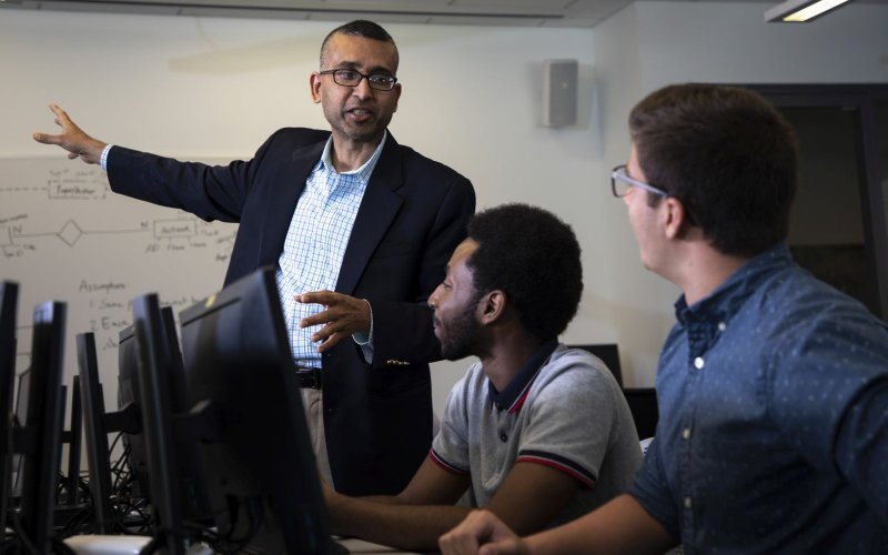 Professor Sanjay Goal gestures toward a whiteboard covered with diagrams while talking to two students seated at a table filled with computers.