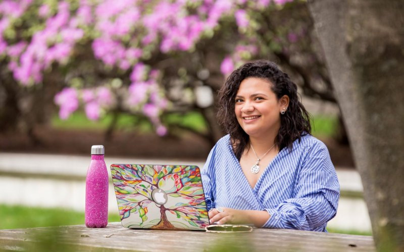 UAlbany student on laptop in garden