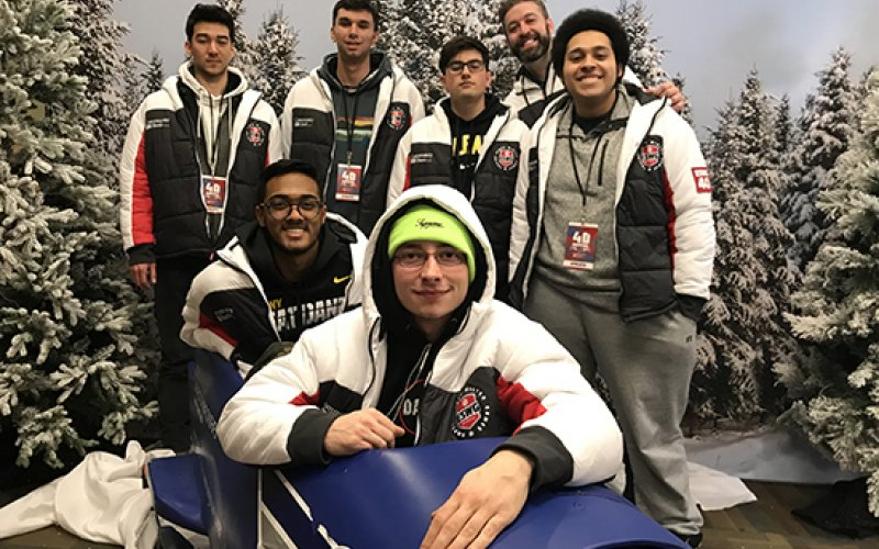 "UAlbany's ""Overwatch"" team takes photo with a bobsled at the Empire State Winter Games in Lake Placid."