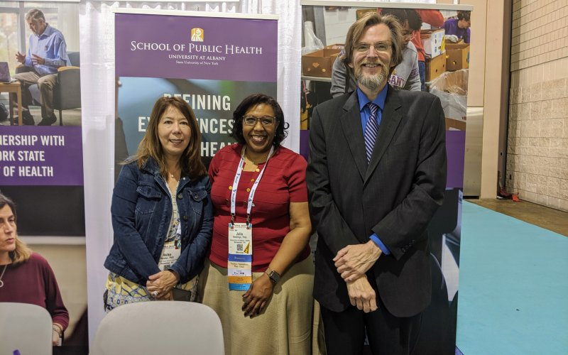 Drs. Hosler, Hastings, and Holtgrave stand behind UAlbany's table at the APHA expo, smiling.