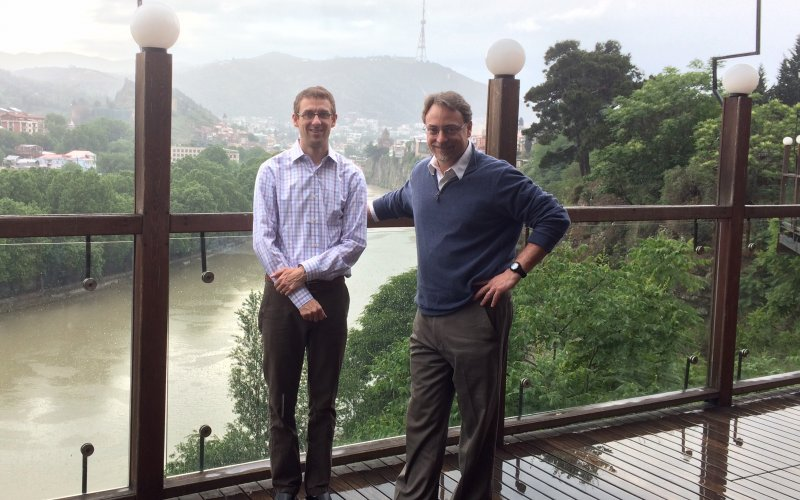 Mark Kuniholm and John Justino stand on a bridge in Georgia. Behind them is a river and mountains dotted with houses.