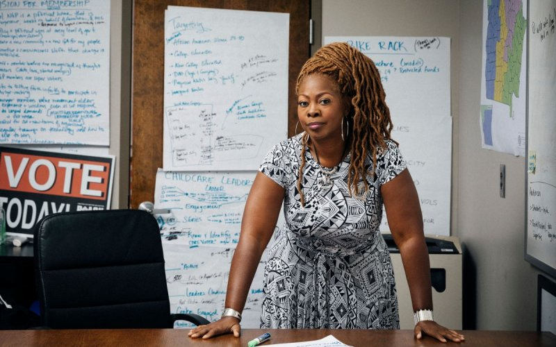 LaTosha Brown stands, leaning on her desk, surrounded by whiteboards covered in writing