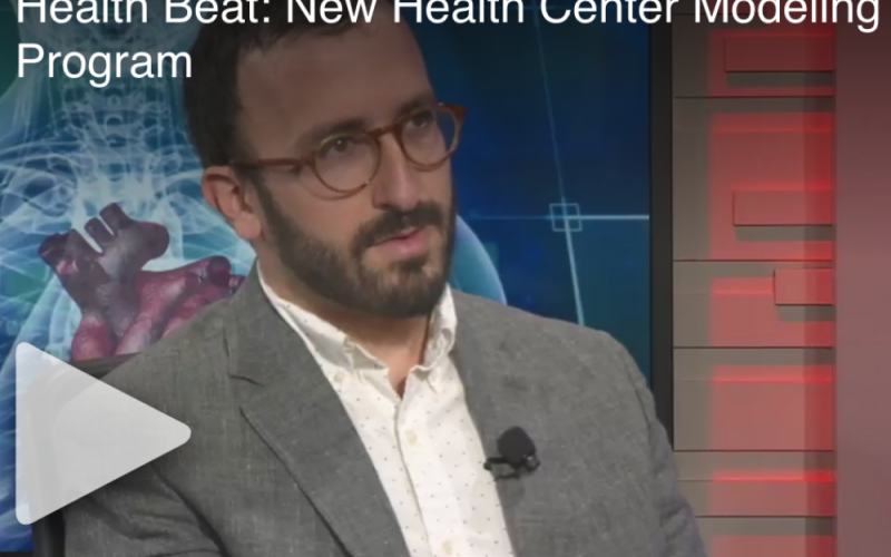 Dr. Eli Rosenberg wearing a grey suit with the health beat set behind him.