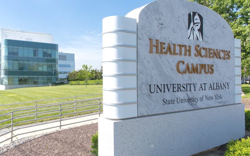 """Health Sciences campus"" sign with a health science building, a blue sky, and bright green grass in the background."