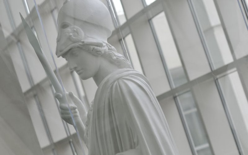 A white statue of Minerva stands in the Science Library atrium. Glass windows are behind her.