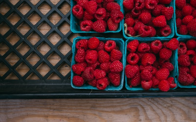 Cartons of raspberries sitting on a wooden table