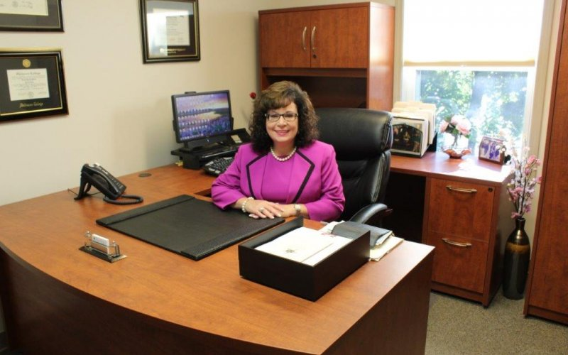 Dr. Nicole MacFarland, wearing a hot pink suit, sits behind her wooden desk in her office at Senior Hope Counseling. She is smiling at the camera.