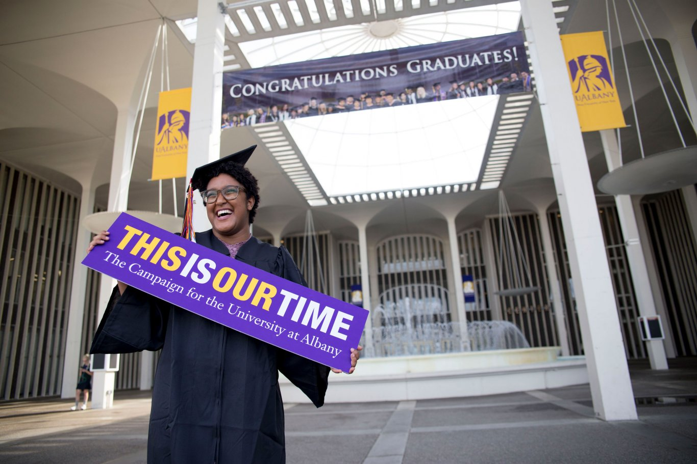 A UAlbany graduate celebrating Commencement poses on the Podium.