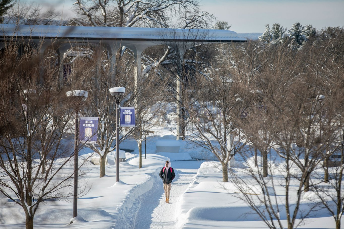 A student walks across UAlbany's snowy Main Campus.