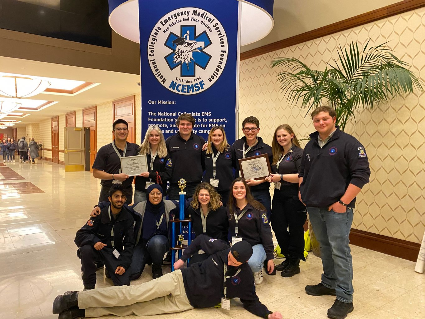 Twelve Five Quad volunteers pose for a photo with plaques and a trophy in front of a National Collegiate EMS Foundation sign