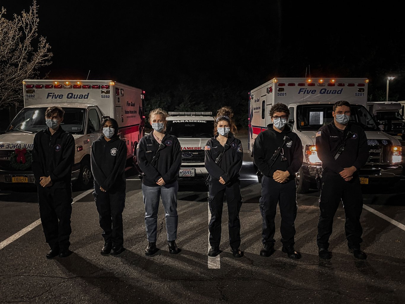Six masked Five Quad volunteers pose for a photo in front of two ambulances and a paramedic's vehicle