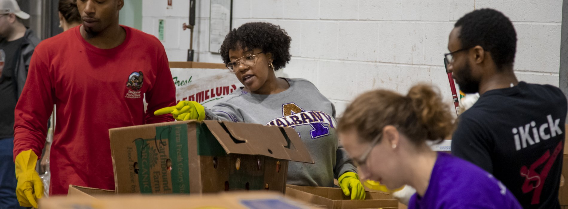 A student at the food bank points at a box of food that needs to be sorted. She is standing behind several boxes of packaged food.