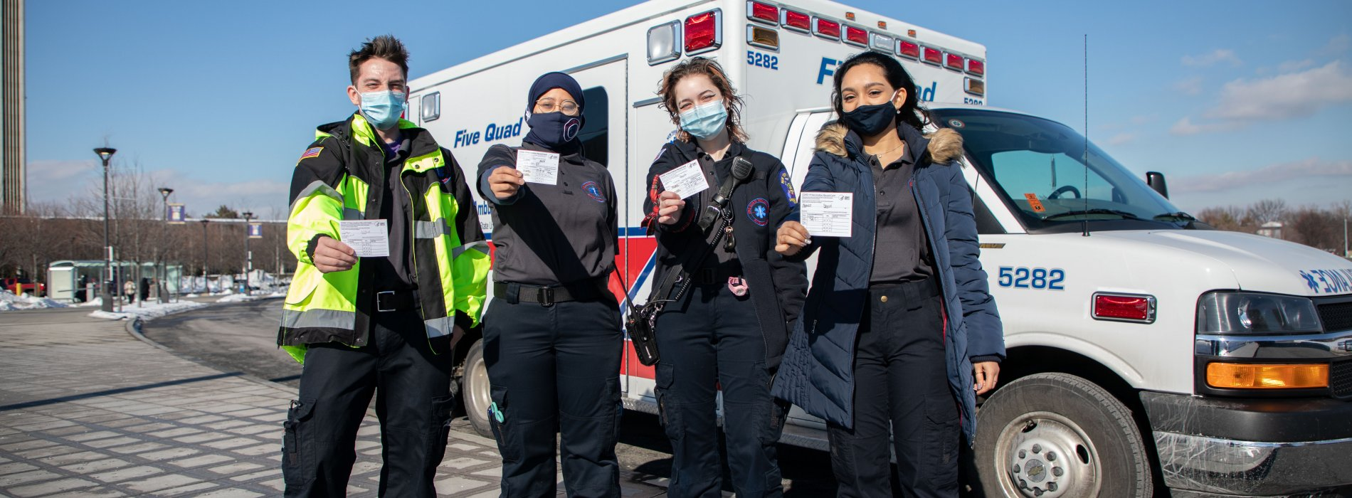Four student EMTs pose in front of the Five Quad ambulance with their COVID-19 vaccination cards