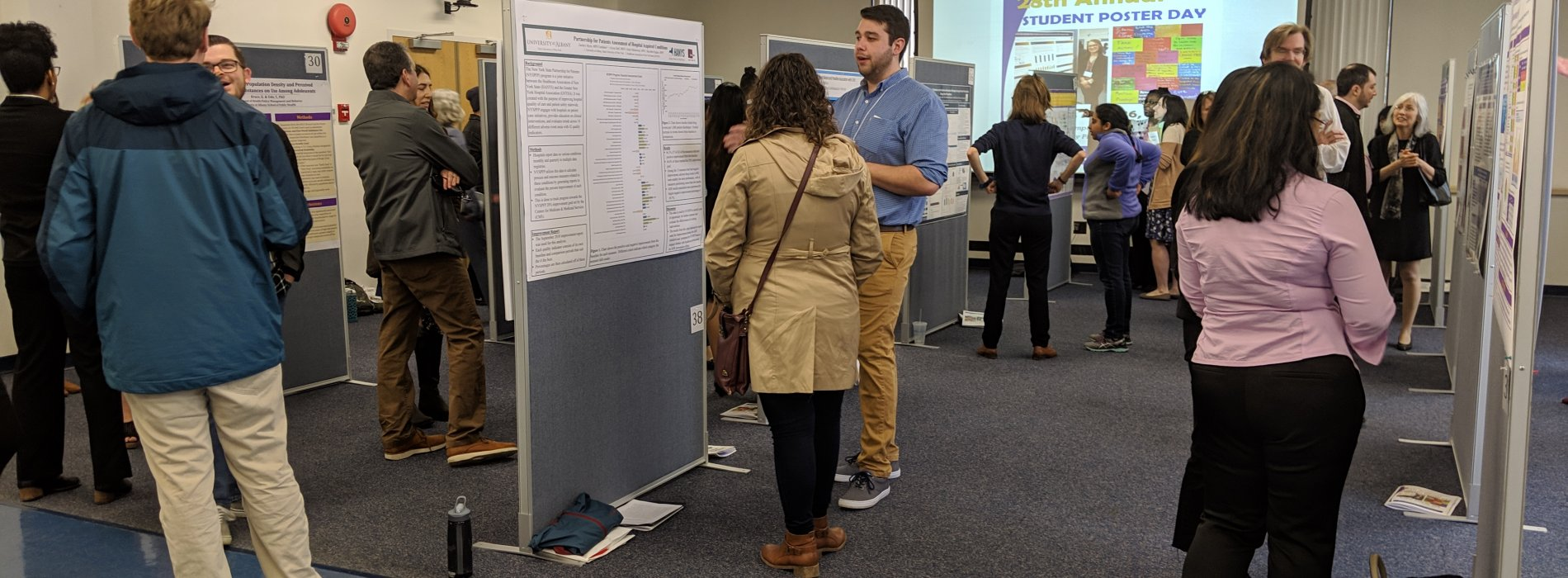Student and faculty talking in front of academic posters