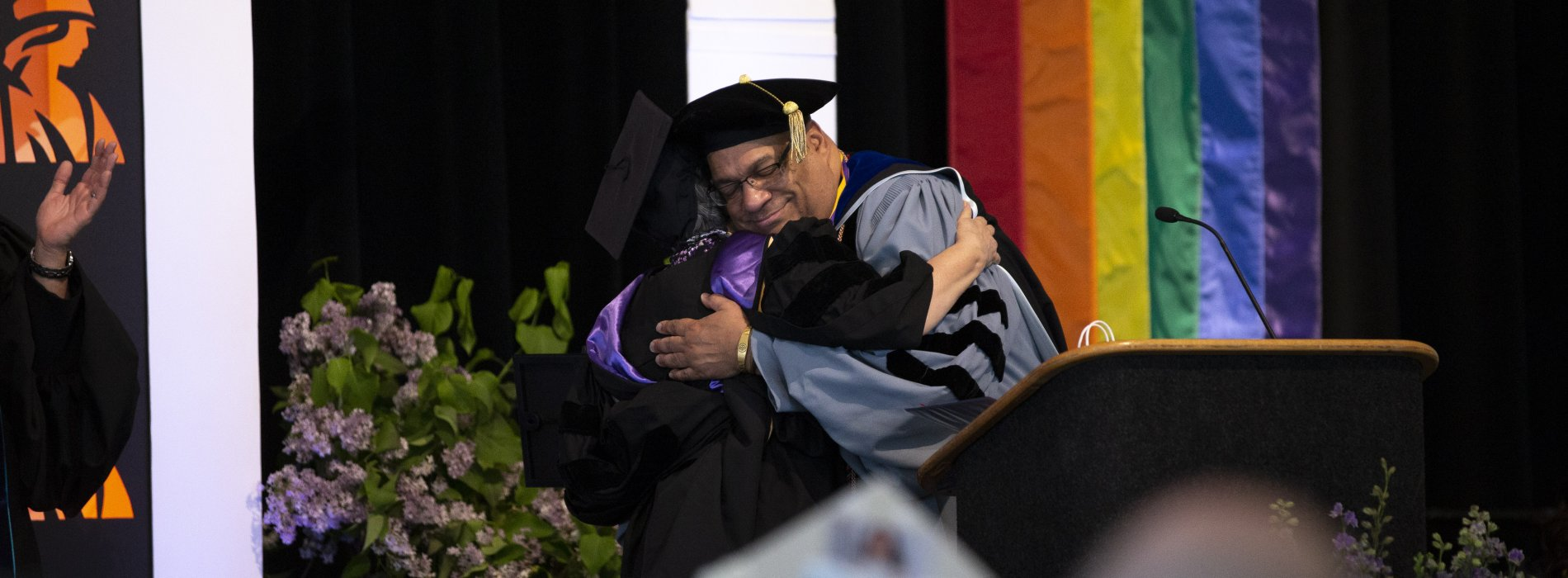 A faculty member hugs a student during the 2019 Lavender Celebration