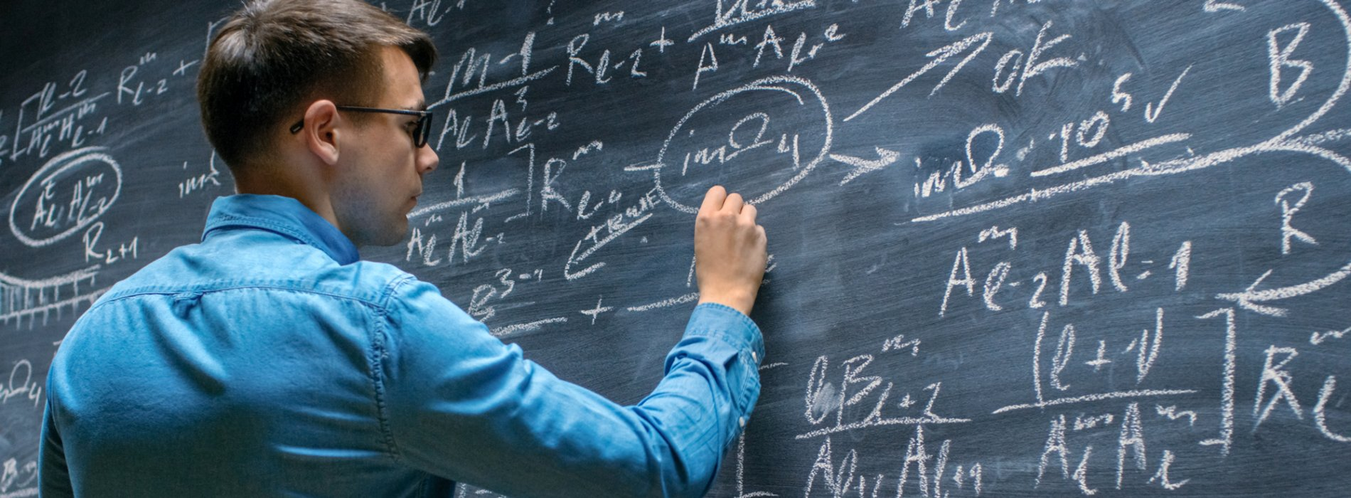Student working on a mathematics formula at a chalkboard