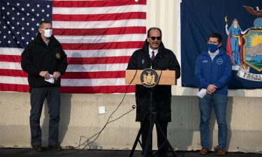 President Rodríguez, stands at a podium placed in front of American and New York State flags speaks during a media event at the state-run COVID-19 vaccination site on UAlbany's main campus.