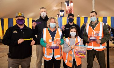 Six people wearing masks and holding bags of donated ear savers pose for a photograph inside a tent.