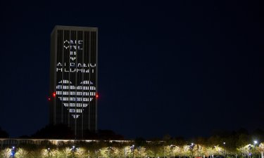 "Eastman Tower on State Quad is lit up with ""One UAlbany"" and a heart."