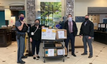 Four people in masks stand besides five boxes of donated food and pose for a photograph inside a hotel lobby.