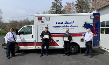 Student volunteers pose in front of a Five Quad ambulance in Rockland County.