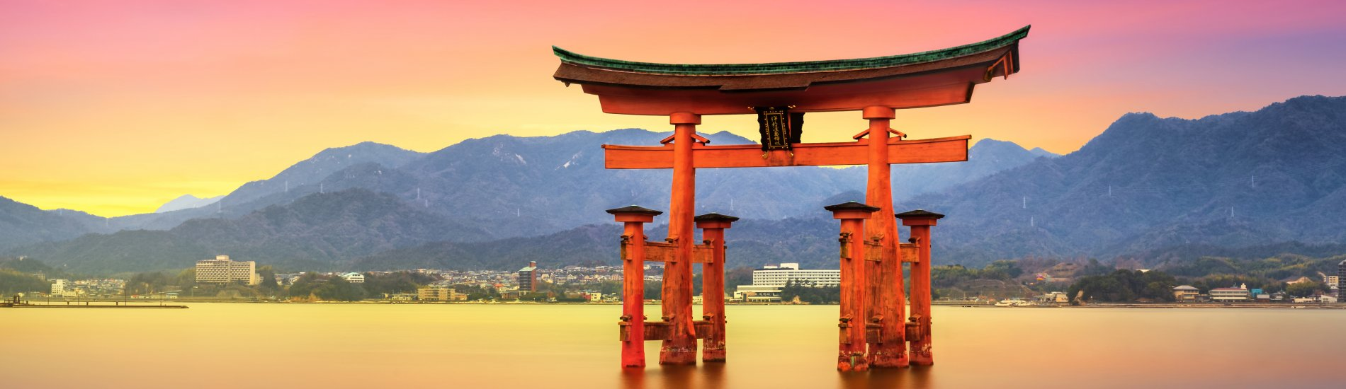 Floating Torii Gate of Itsukushima Shrine off the coast of Miyajima Island in Japan at sunset.