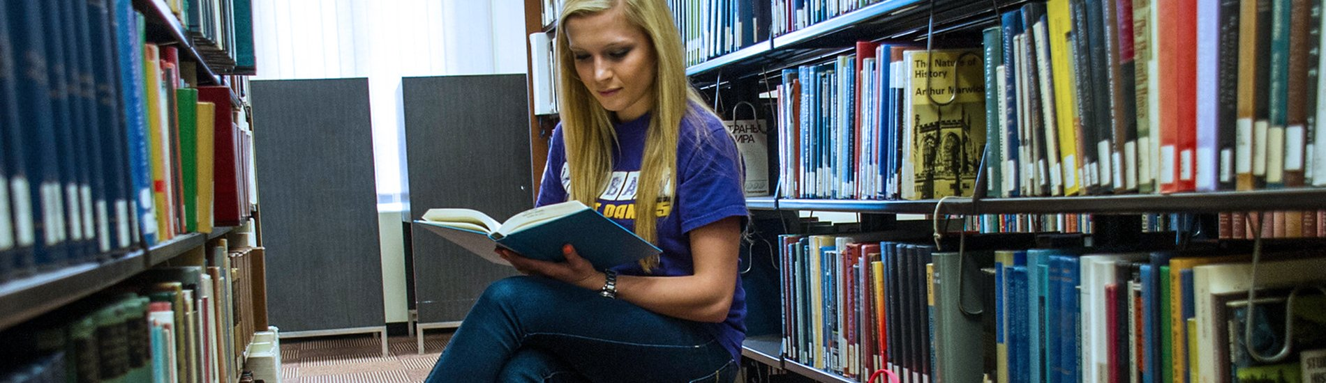 Female student reading a book in the stacks of the UAlbany library