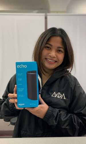 Woman With dark brown hair smiling, holding amazon echo box in front of gray wall.