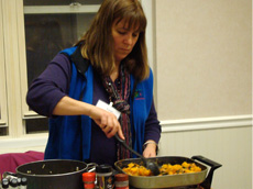 A person from the Cornell Cooperative demonstrates healthy cooking at the Holiday Health Fair of the Women's Health Project